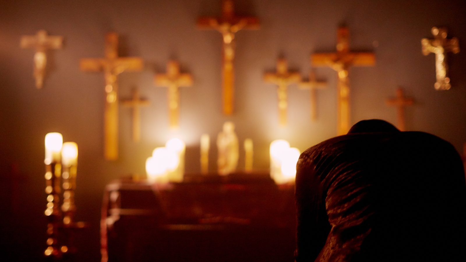 A man with his head down praying in the foreground. In the background a wall covered in crucifixes and candles underneath.