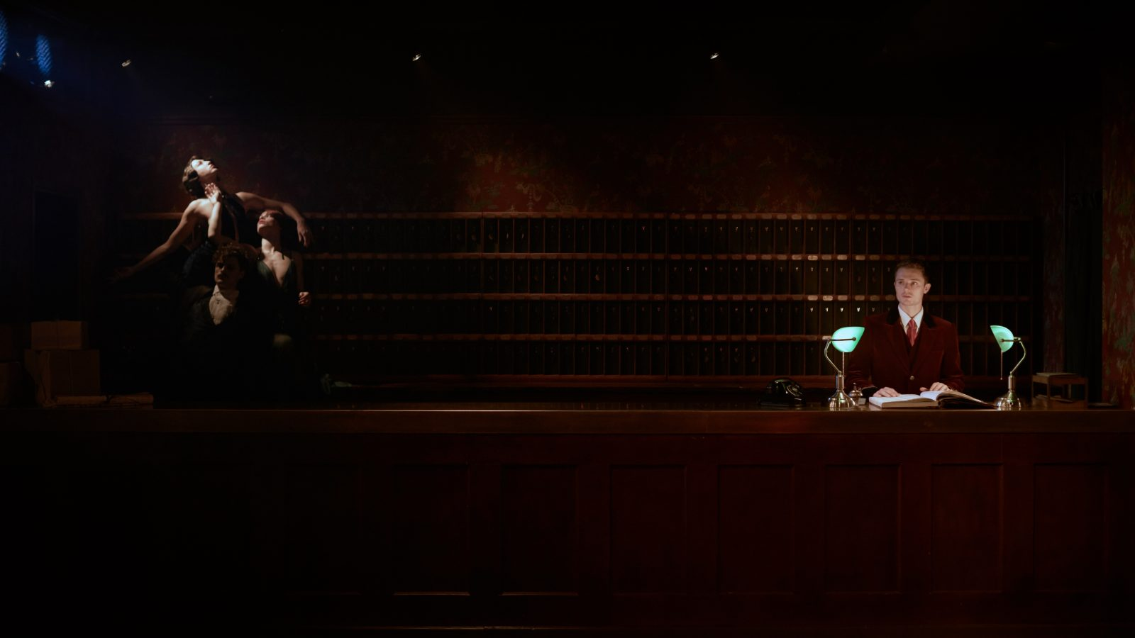 A dark hotel reception. A porter on one side of the image, on the left a group of dancers lift eachother up.