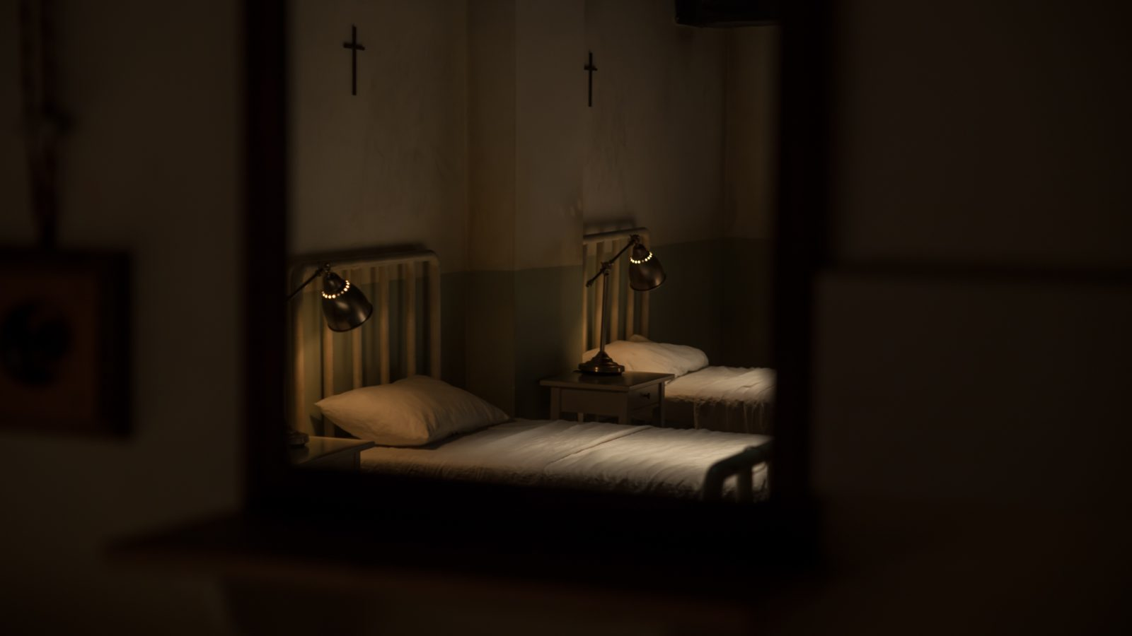 Two 1930s hospital beds with anglepoise lamps. A crucifix is above each bed,