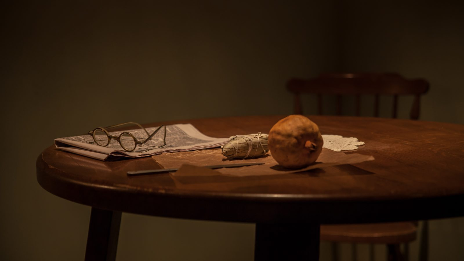 Glasses, newspaper and ball of string on a table,