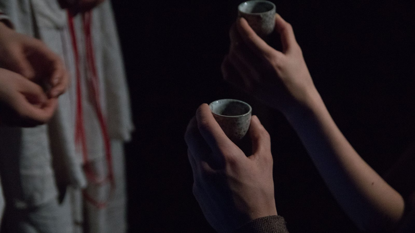 Two hands hold small clay cups upwards towards two unseen women.