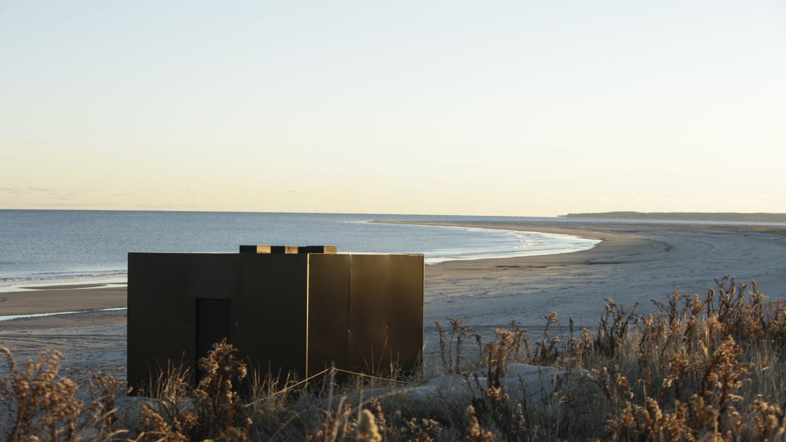 Small black rectangular building on a beach
