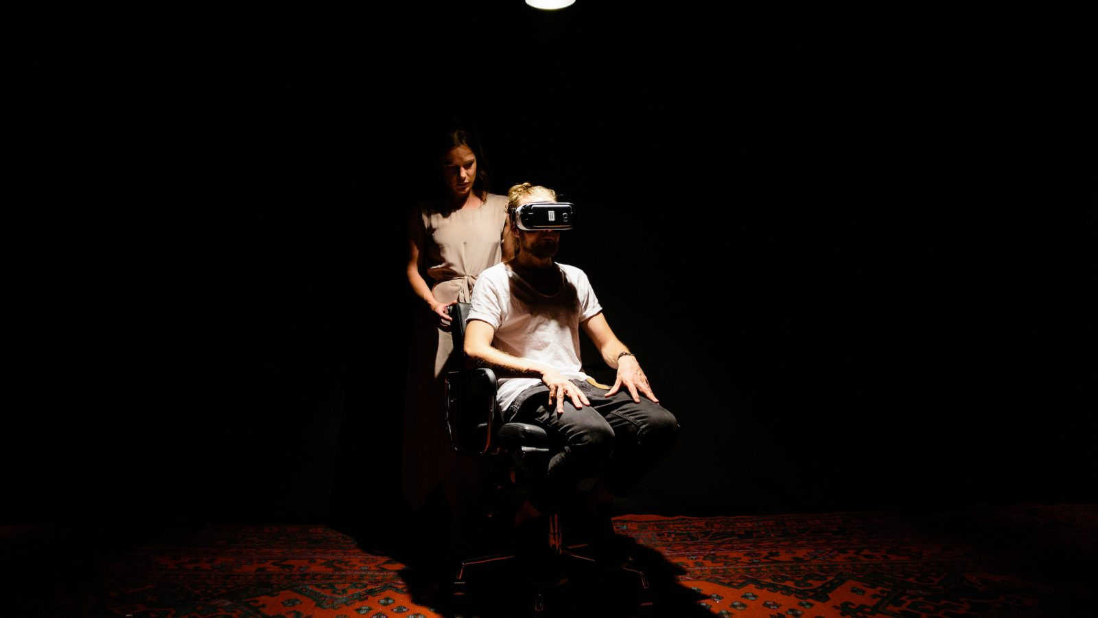 A woman stands behind a man wearing a VR headset in a darkened room.