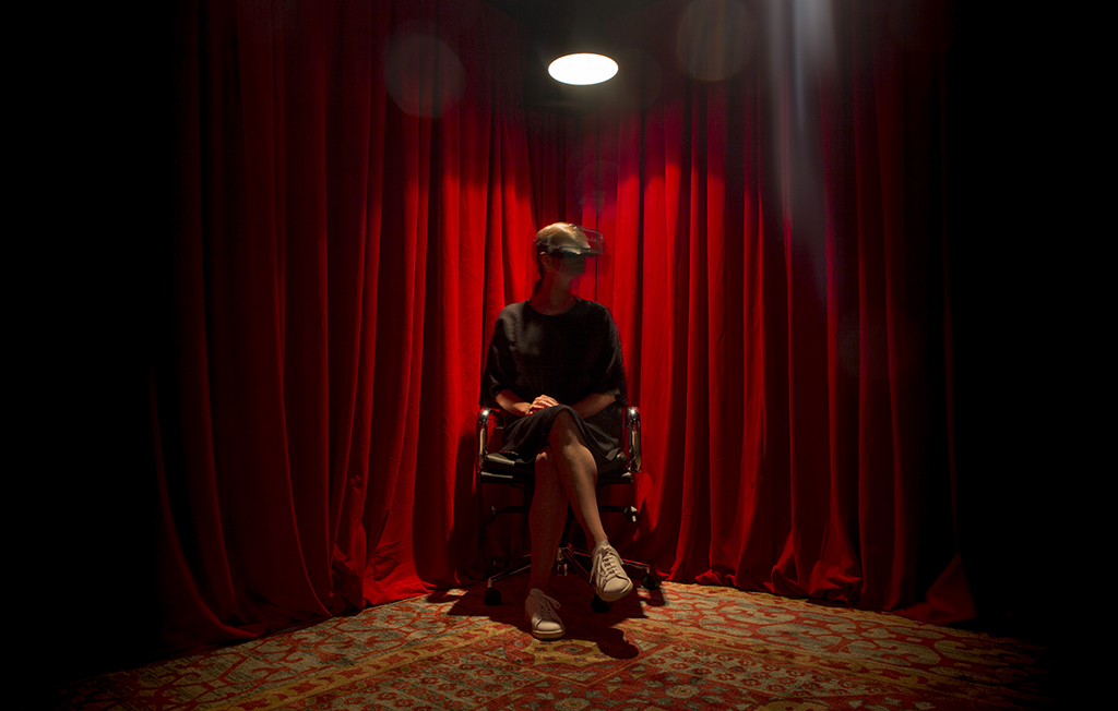 A woman in a black dress wearing a VR headset sits underneath a spotlight. A red curtain in the background.