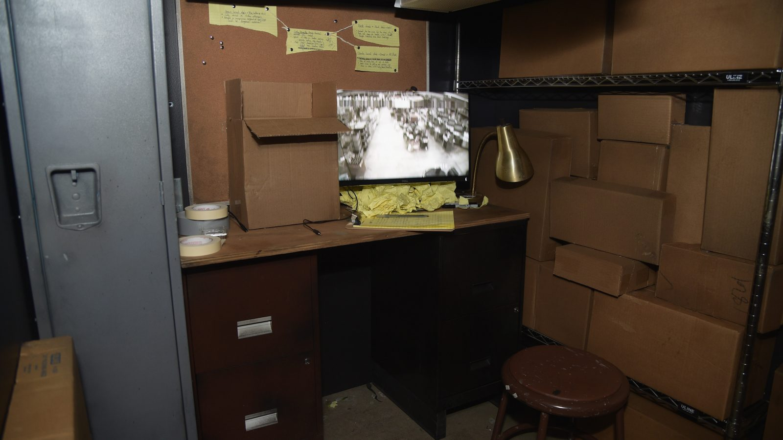 A store room full of boxes with a computer screen showing CCTV.