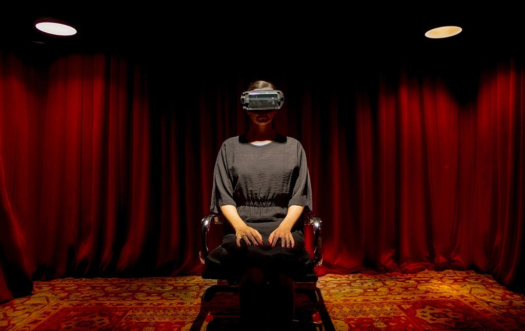 A woman wearing a black dress and a VR headset sits in the middle of the image with two spotlights either side of her and a red curtain in the background.