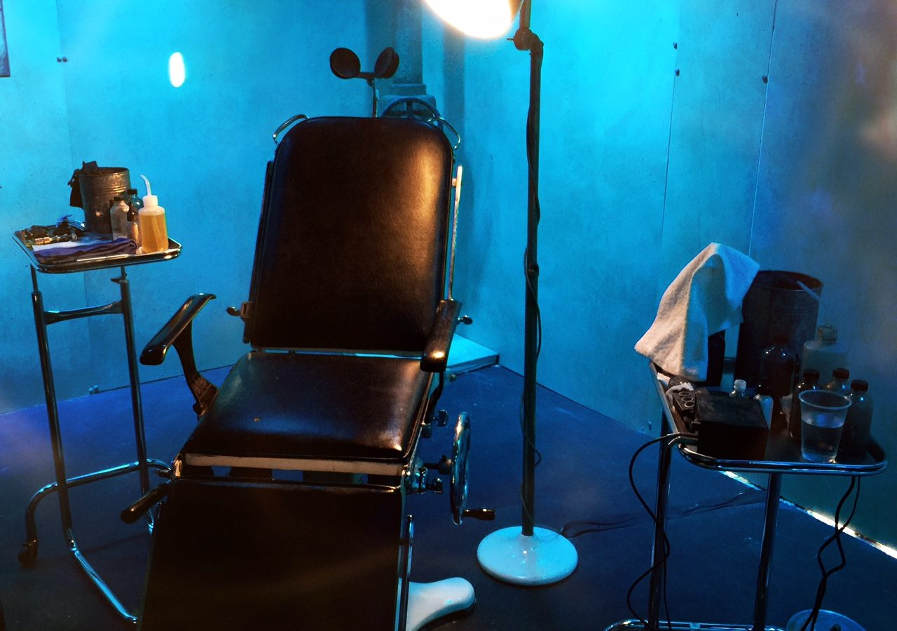 Empty tattoo chair in a dark room with a lamp