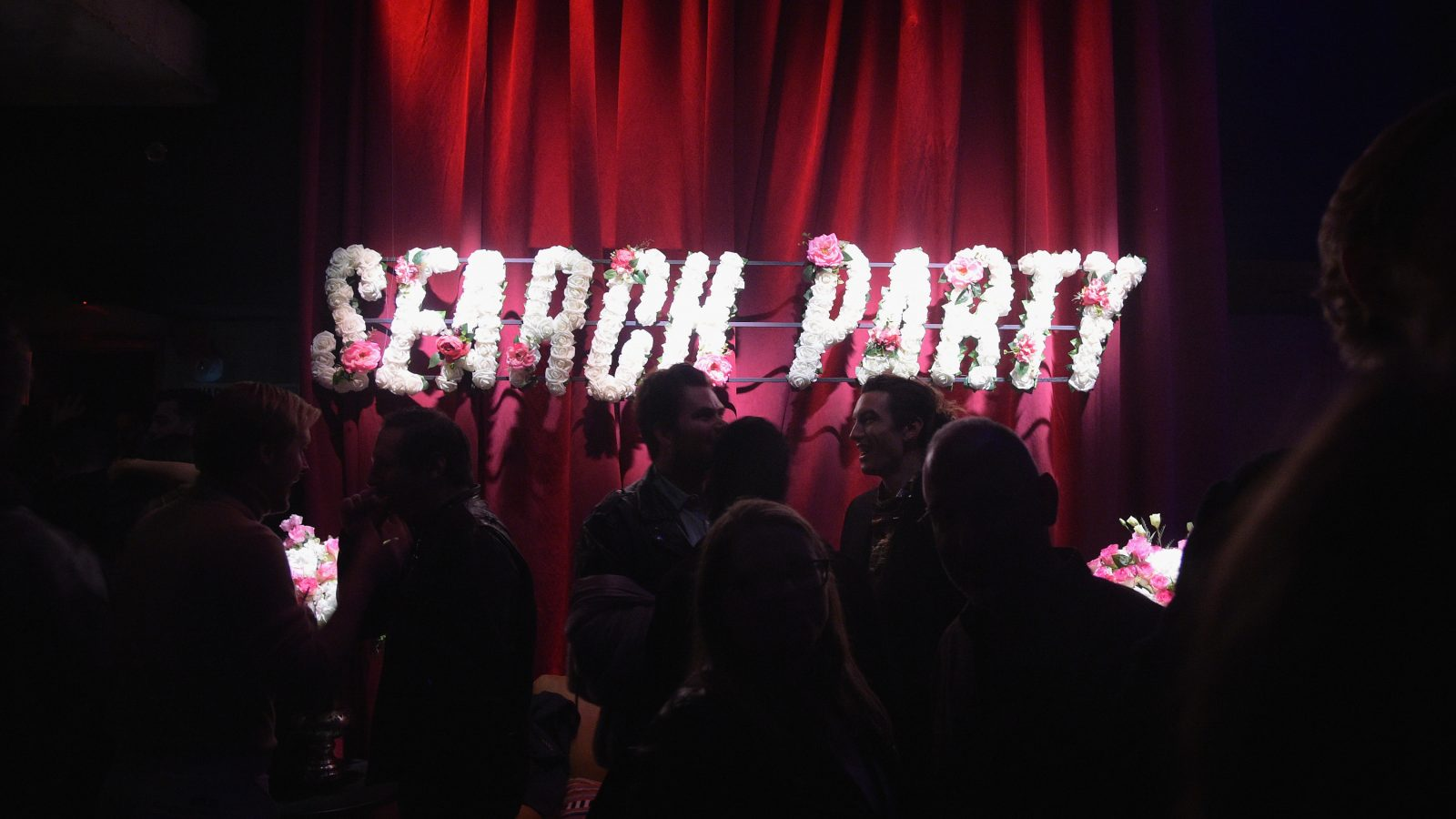 Search Party in letters made of white flowers hanging on a red curtain.