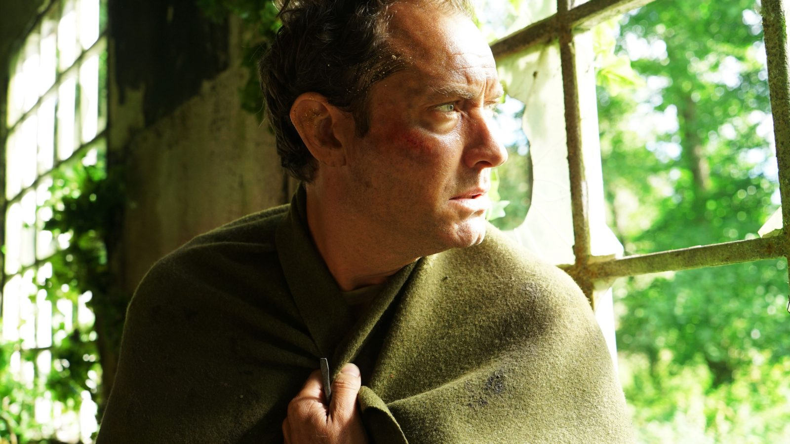Jude Law wrapped in a green blanket staring out of a window with a frightened look on his face. Part of The Third Day TV series.