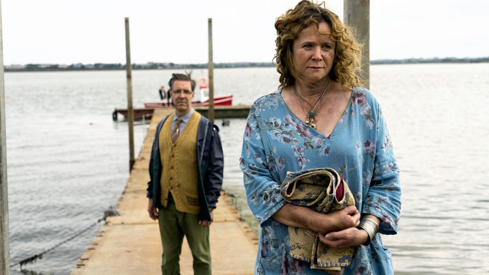 Emily Watson and Paddy Considine stood on a wooden pier stretching out to sea. Part of The Third Day TV series.