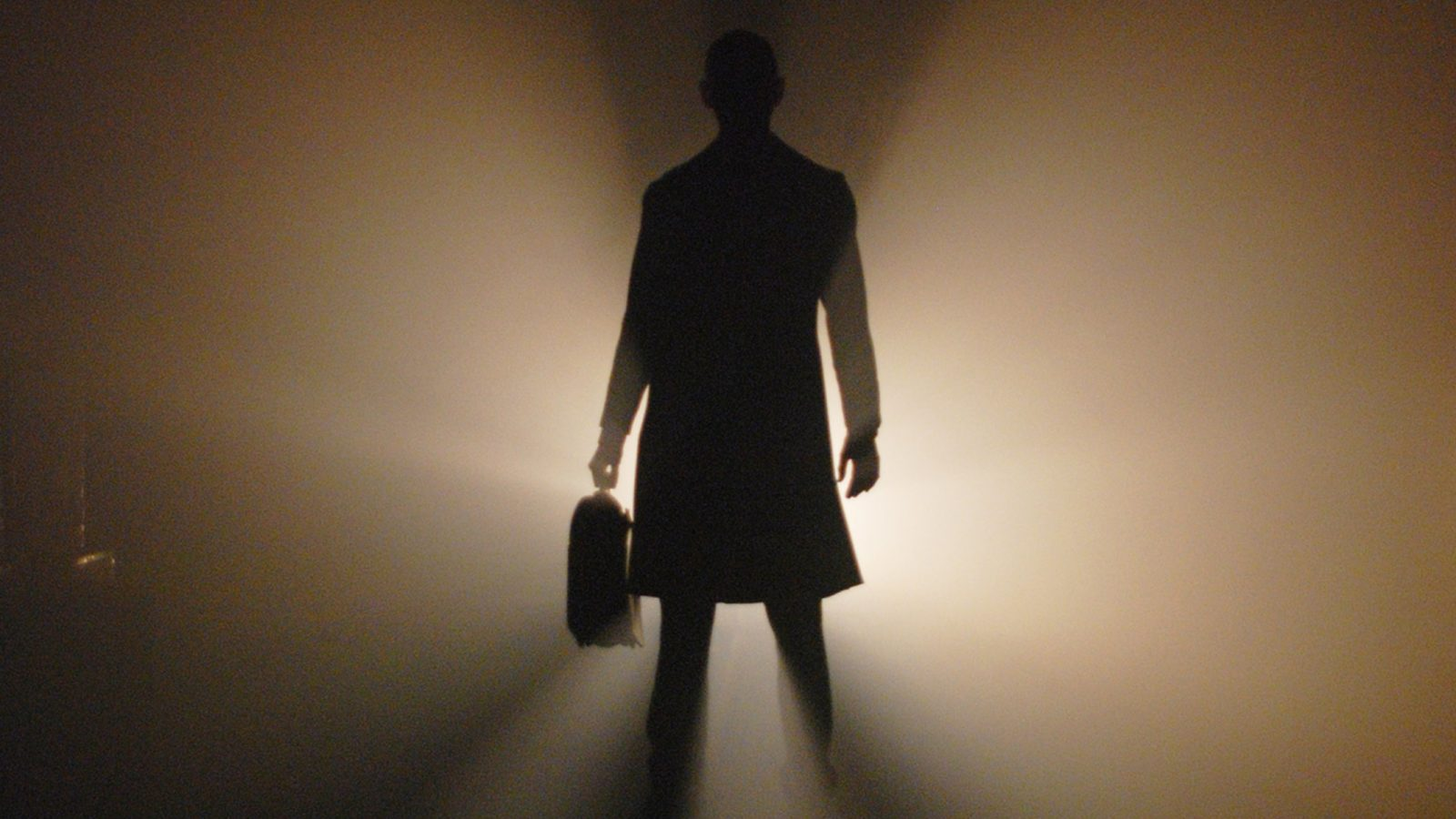 Silhouette of a person standing in front of a light