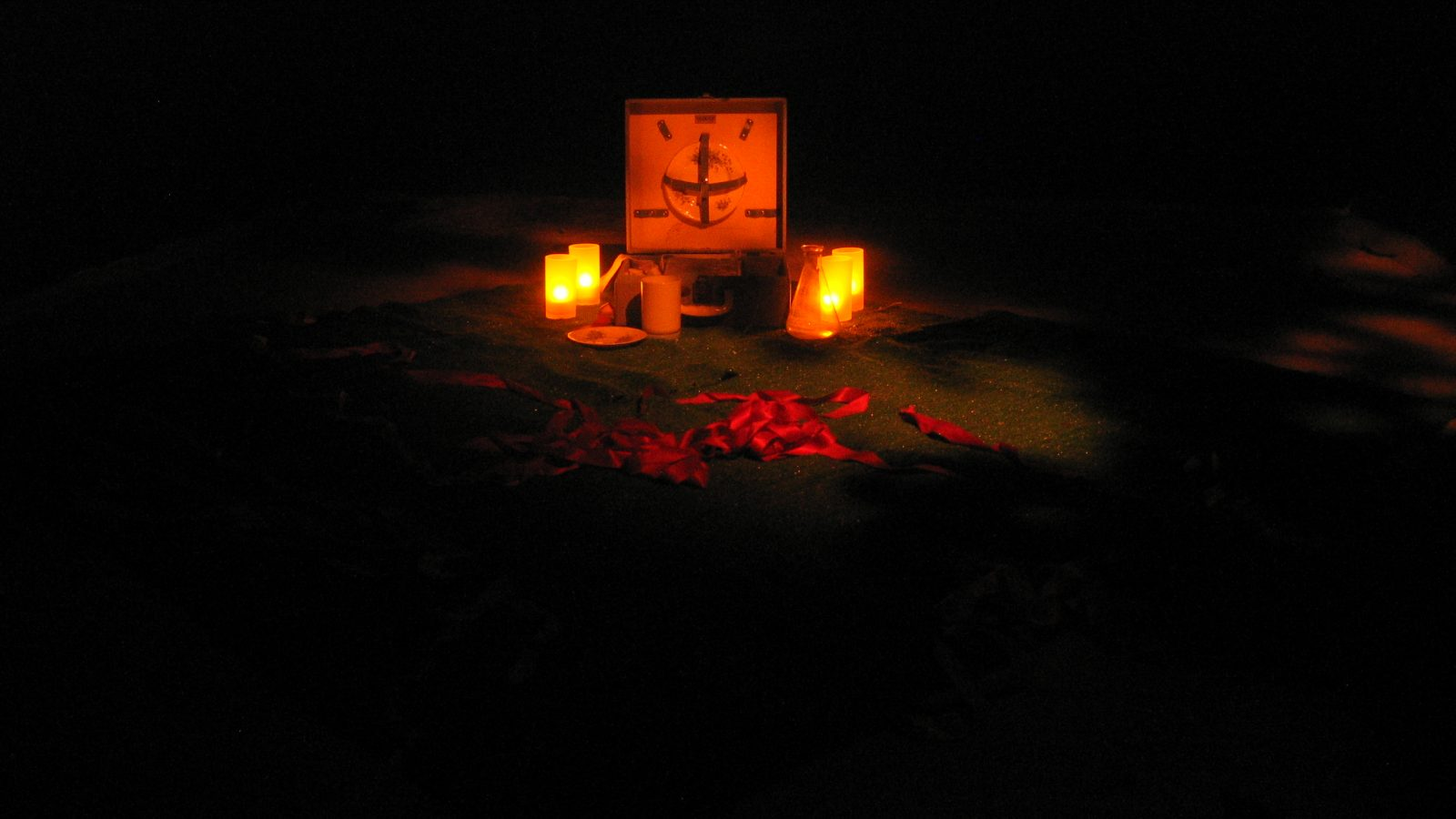Candles, ribbons and box ornament on the floor, dimly lit