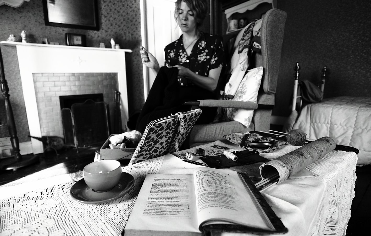 Woman sewing in the background; table with books, cups and various items in foreground