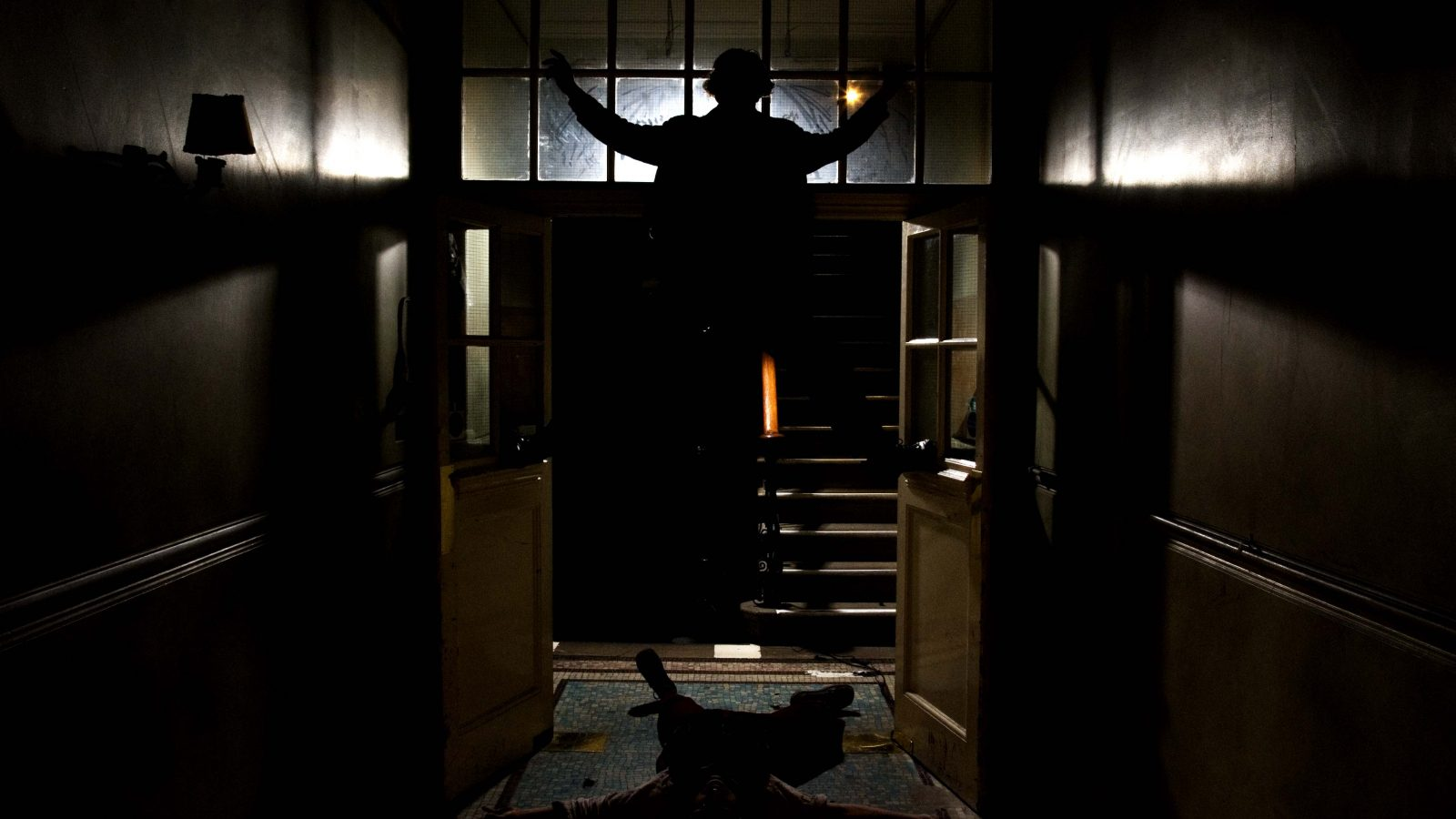 Silhouette of a man standing above another man on the floor of a hallway