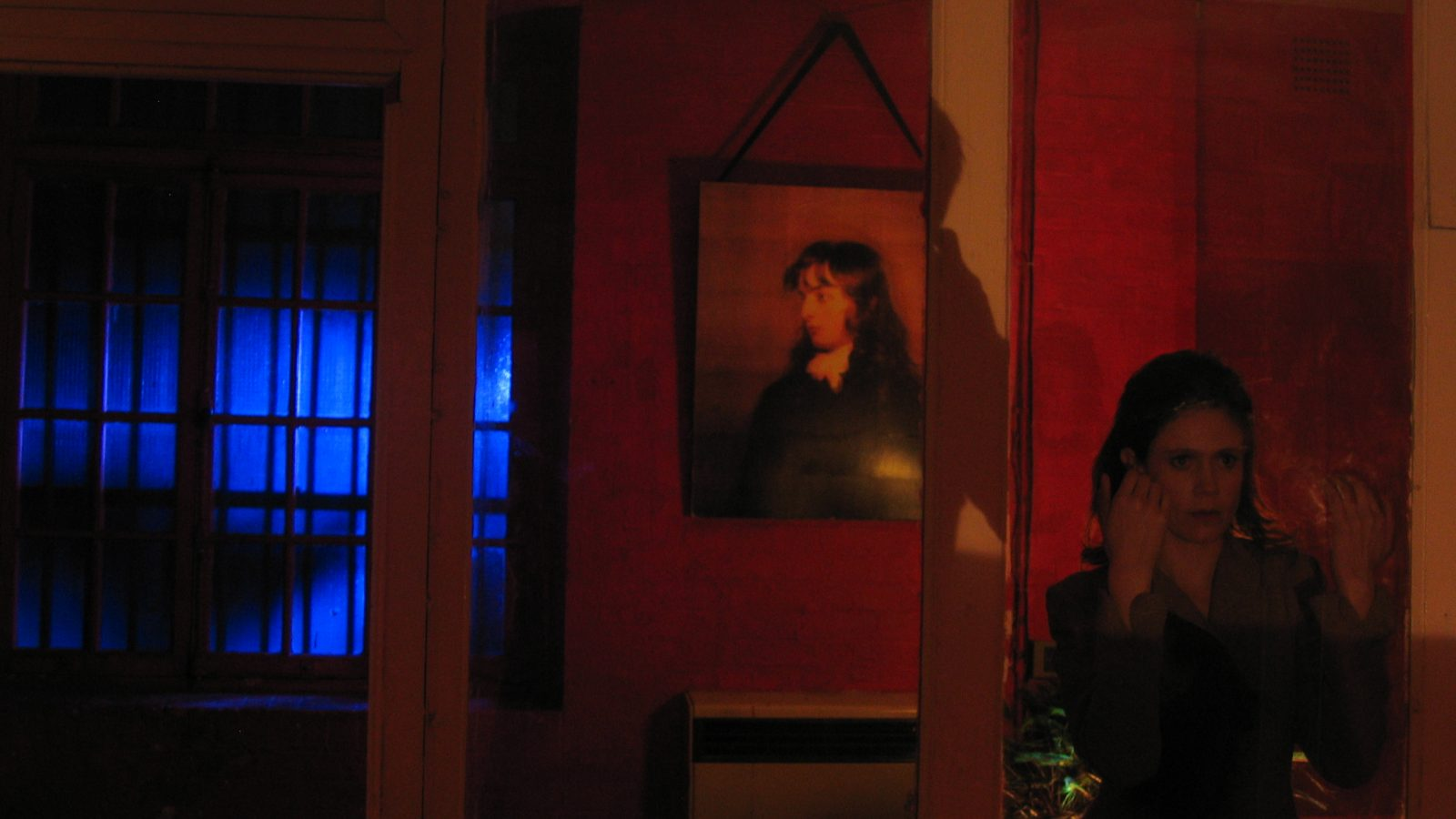Woman standing in front of clear door frame, old painting and blue window in the background