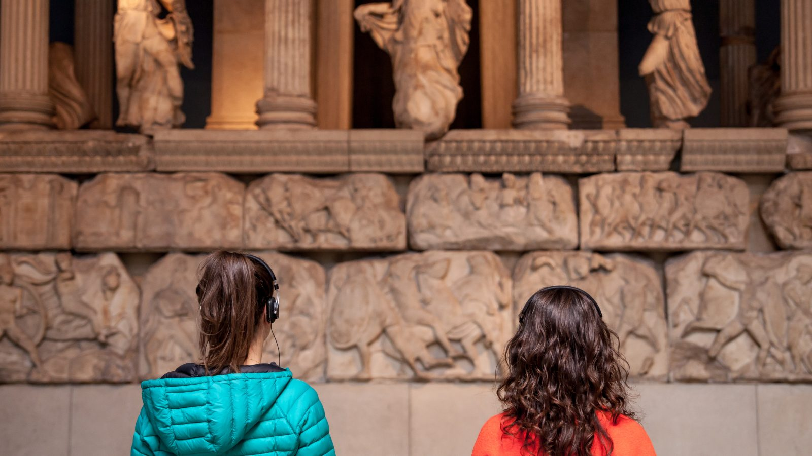 Two women wearing headphones in front of an exhibit at the British Museum.