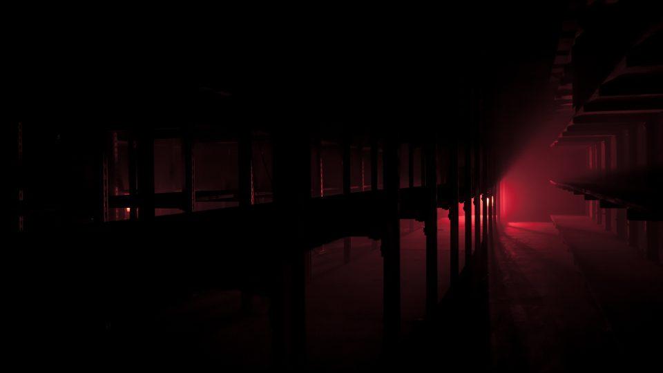 Low red light shining through shelves.