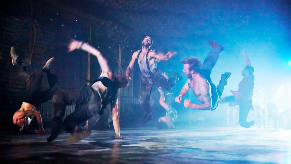 Three male dancers all in the air in blue light.