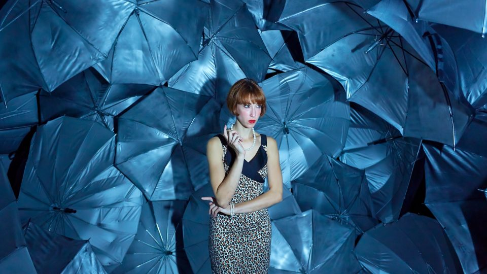 A woman stood in front of a wall of blue umbrellas smoking.