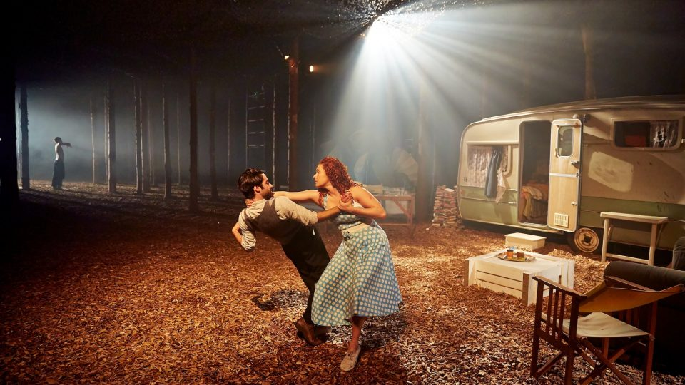 A man and woman dancing. Woodchip on the floor, a caravan in the background.