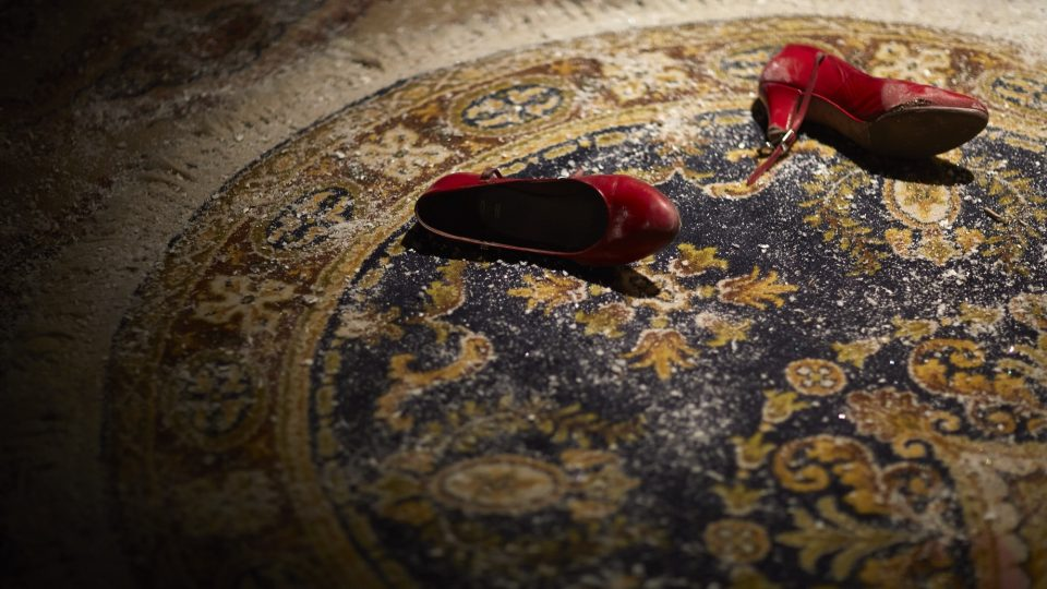 Pair of red shoes on top of a dusky rug
